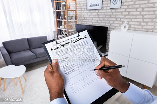 Close-up Of A Man's Hand Filling Real Estate Appraisal Form With Pen