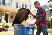 istock Man Filling Recycling Bin On Suburban Street 904482334