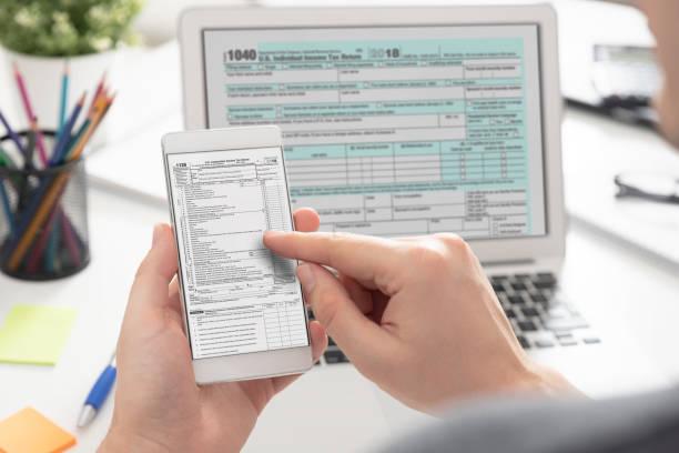 mann füllt steuerinformationen mit mobilen geräten - elektronik industrie stock-fotos und bilder