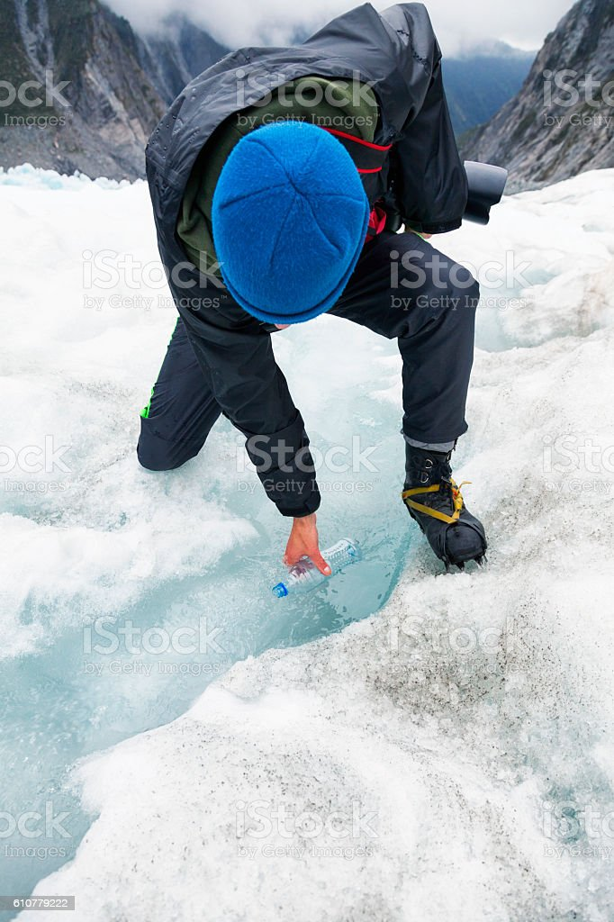 Glacier hiker filling a water bottle from a stream on Franz Josef...