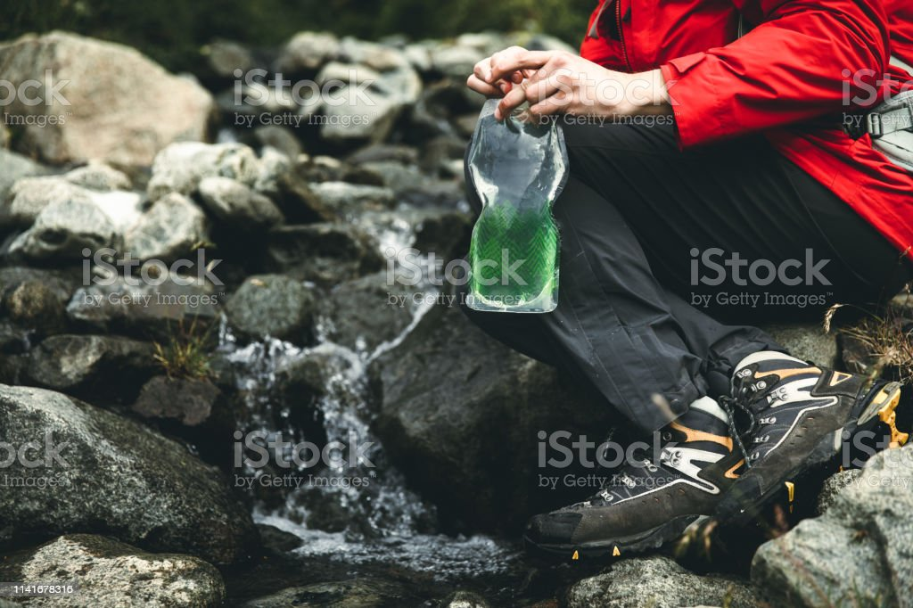 Man filling water from pure glacial river during his hike in Chilean...