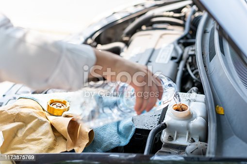 istock Man filling water into the car boiling tank 1173875769
