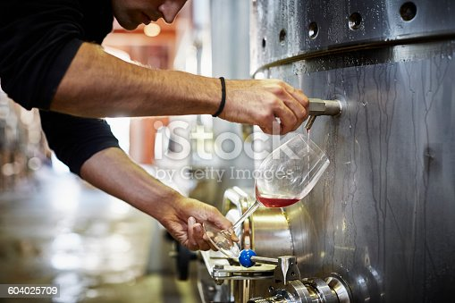 Cropped image of man filling wine from storage tank in winery