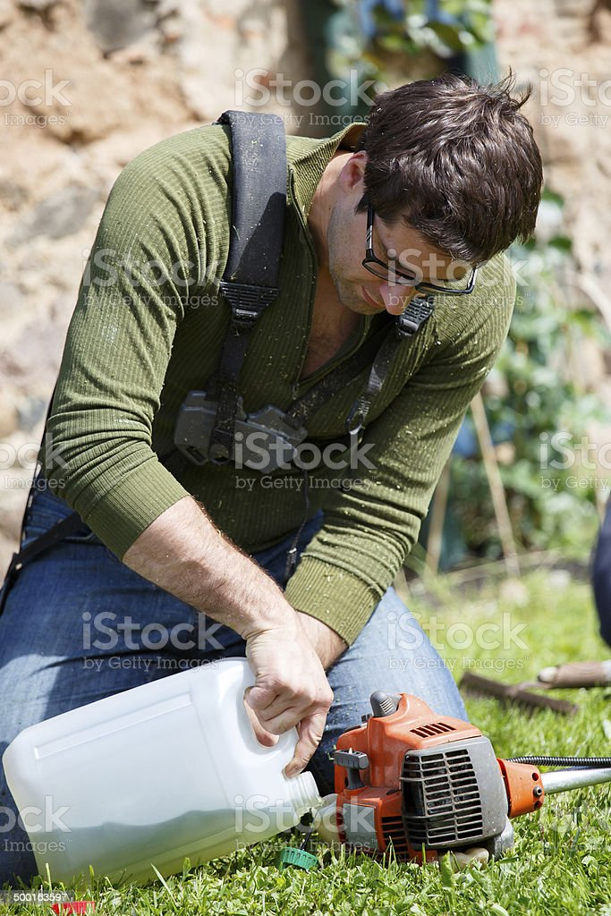 Man fills grass trimmer with gasoline stock photo