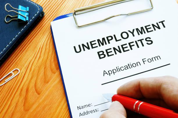 man fills in unemployment benefits application form. - unemployment стоковые фото и изображения
