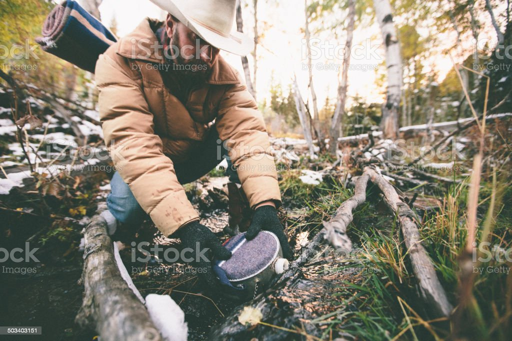 Man fills water canteen while hiking through woods during winter stock photo
