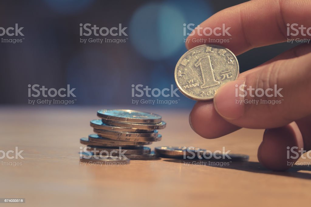 A man finger holding a coin with coin stack on bokeh background and apply matte filter royalty-free stock photo
