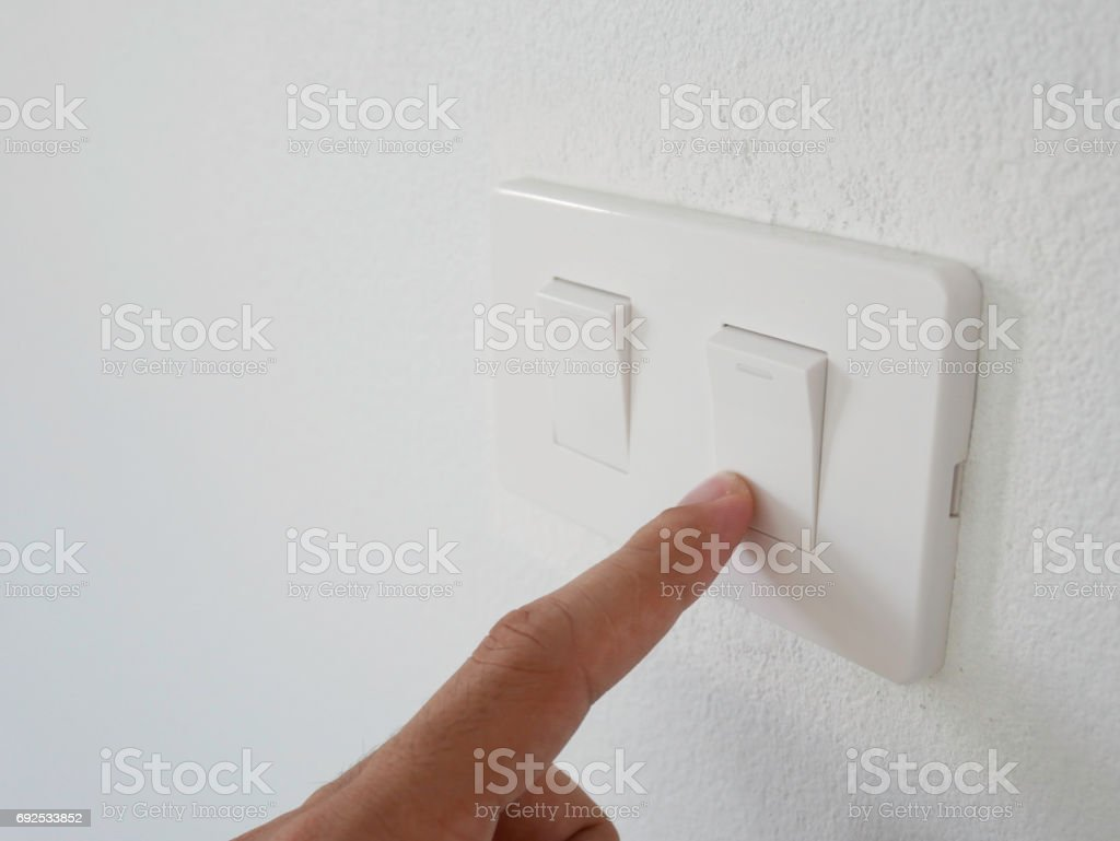 man finger press white switch off light on white wall stock photo