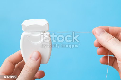 Man fingers holding new white plastic container with dental floss on pastel blue background. Teeth hygiene concept. Closeup. Point of view shot.