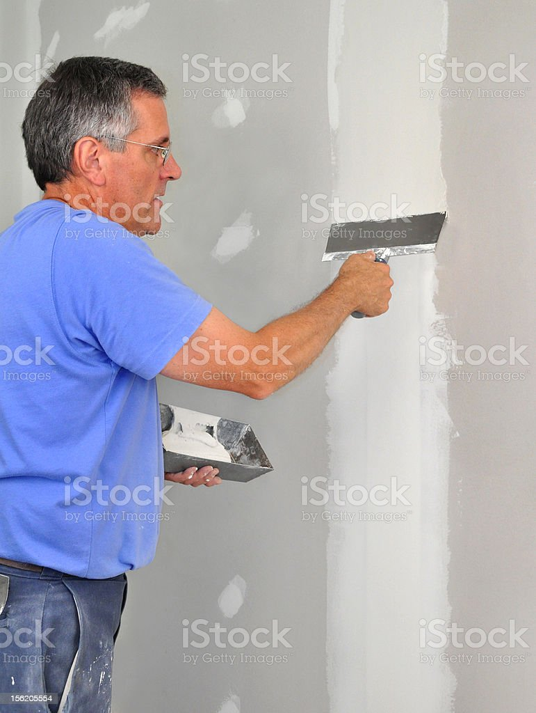 Man finishing seams in drywall royalty-free stock photo