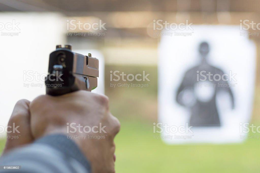 Man Firing Pistol at Target in Shooting Range stock photo