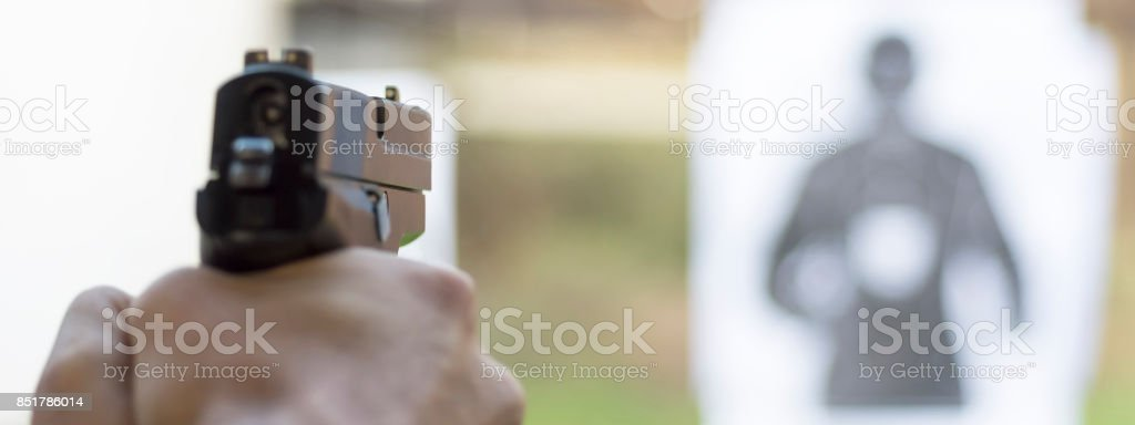 Man Firing Pistol at Target in Shooting Range stock photo