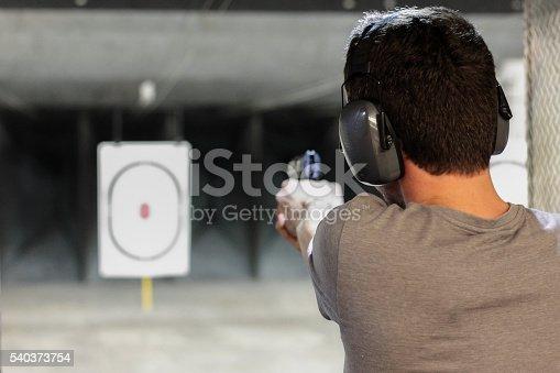 istock man firing usp pistol at target in indoor shooting range 540373754
