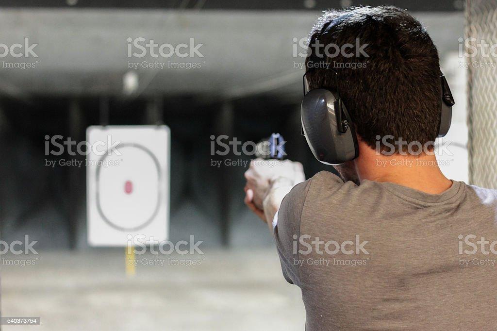 man firing usp pistol at target in indoor shooting range stock photo