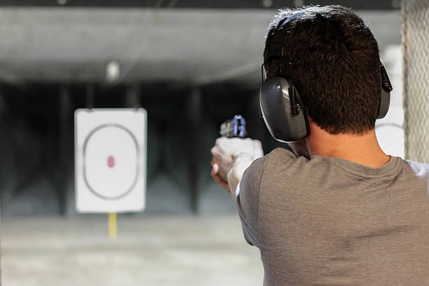 man firing usp pistol at target in indoor shooting range Photo taken at firing range in Orlando Florida shooting a weapon stock pictures, royalty-free photos & images