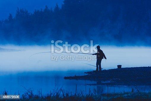 688562434 istock photo Man fishing at river shore 488579506