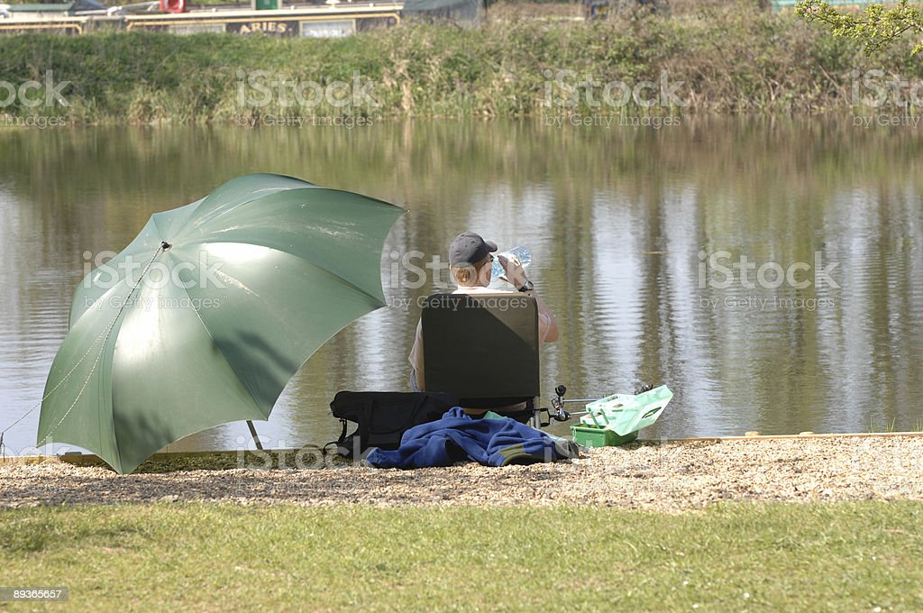 man fishing by river on summers day royalty-free stock photo