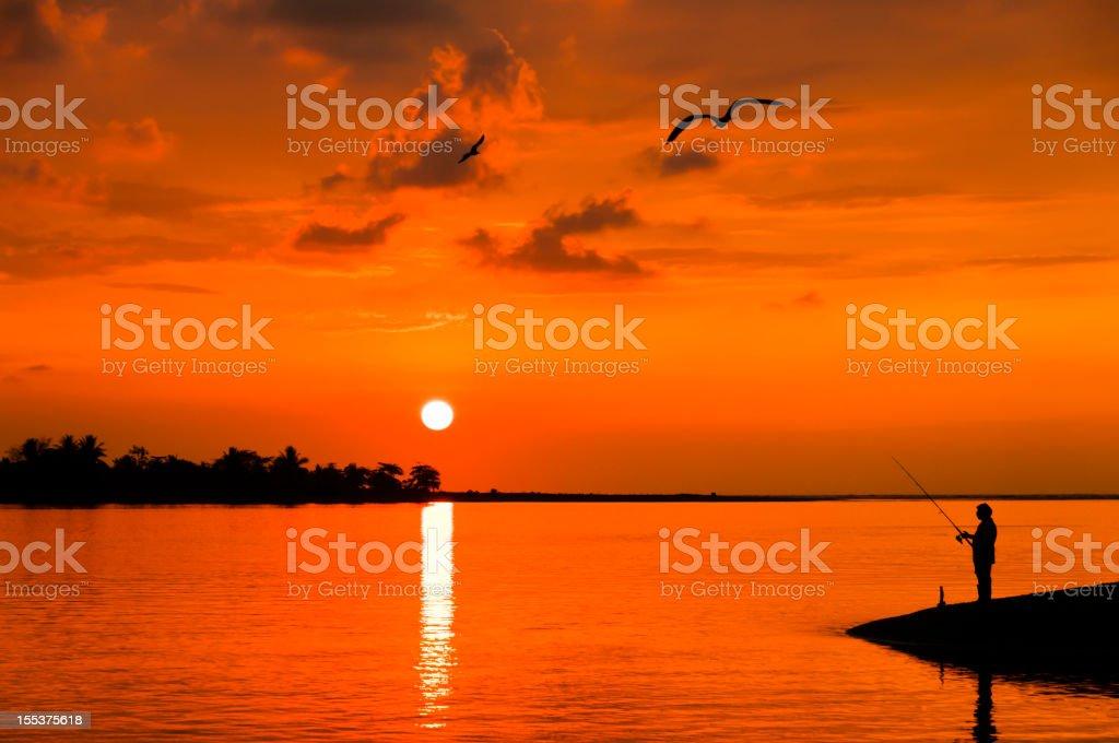 Man fishing during sunset royalty-free stock photo