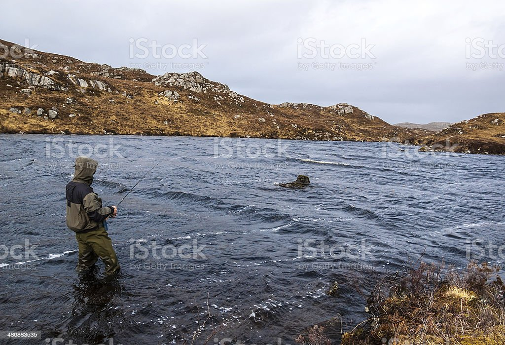Man fishing for trout and salmon in a Scottish loch stock photo