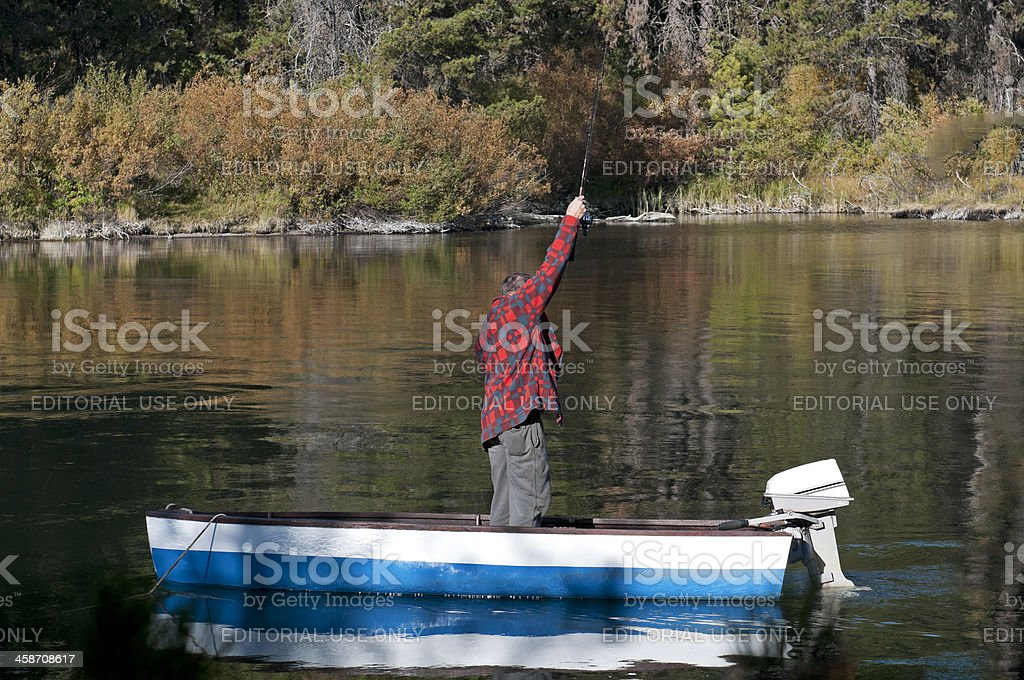 Man fishing for trout from motorboat in river royalty-free stock photo
