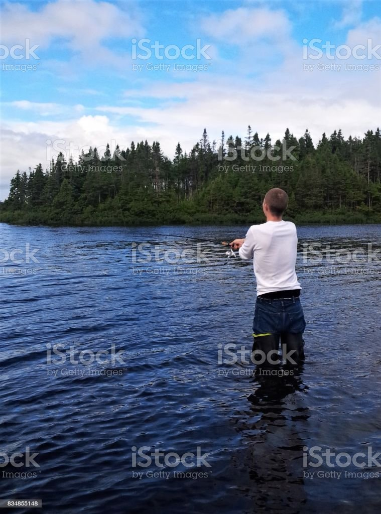 Man fishing in lake, Markland, Newfoundland. stock photo