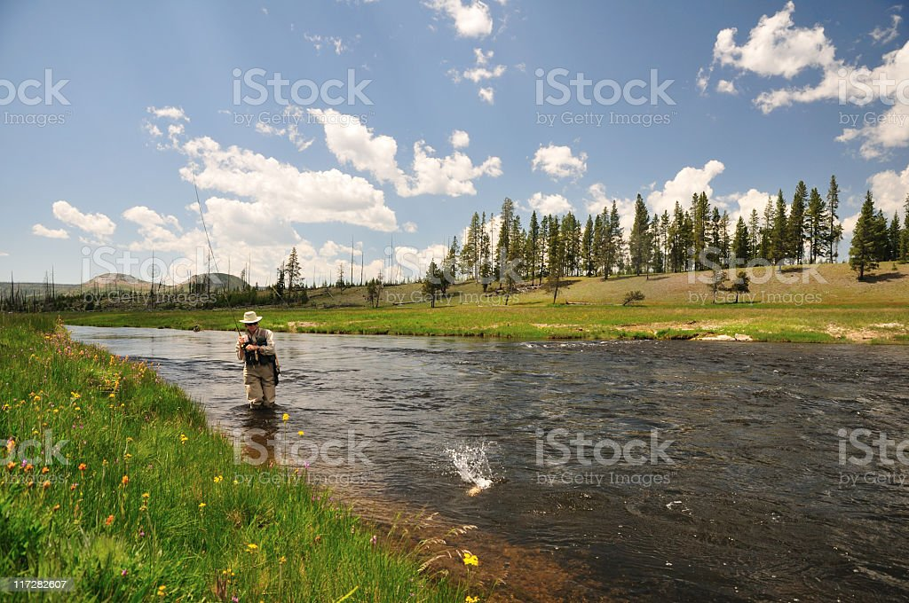Man fishing in river with something splashing in water stock photo