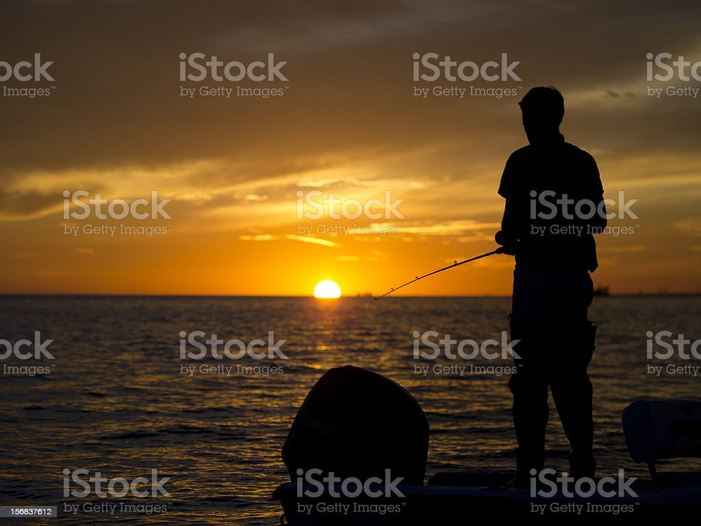 Man fishing off back of boat at sunset stock photo