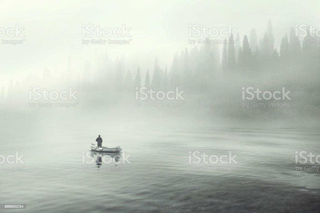 Homem pescando em um barco em um lago enevoado mistic foto de stock royalty-free