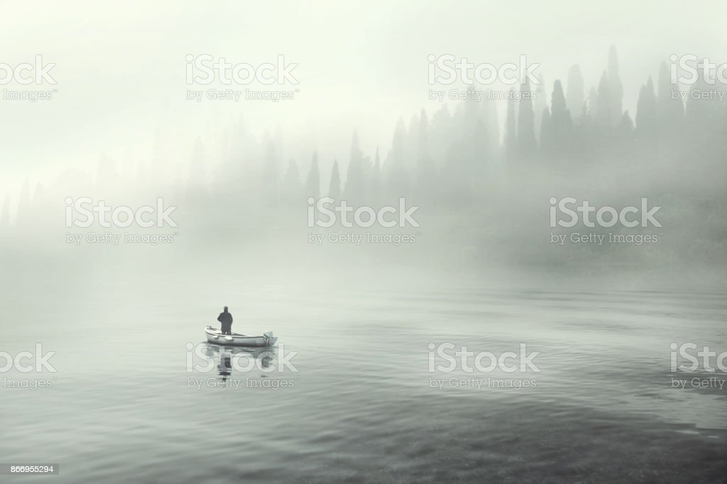 Man fishing on a boat in a mistic foggy lake stock photo