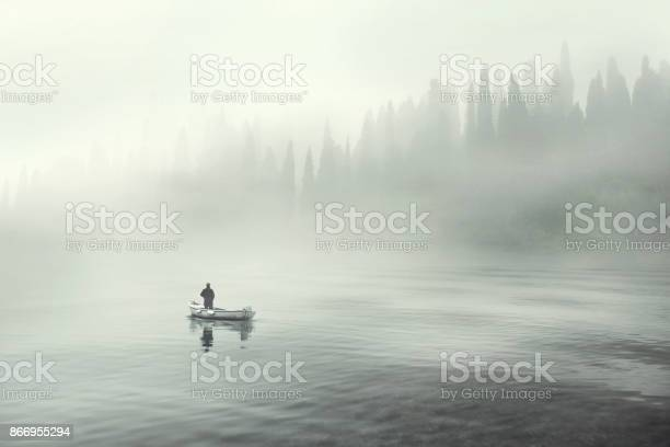 Photo of Man fishing on a boat in a mistic foggy lake