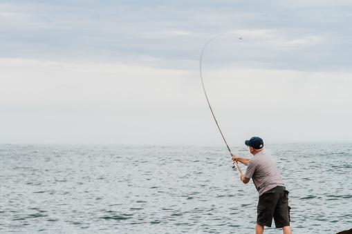 Man fishing on a breakwater of the Atlantic Ocean