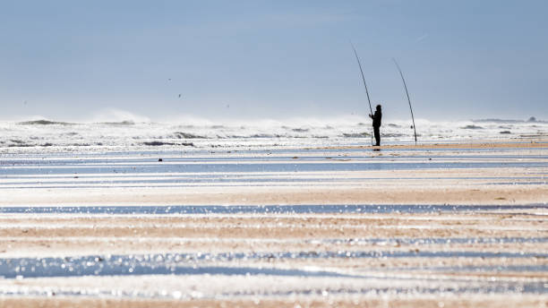 Man fishing on the beach in bright daylight stock photo