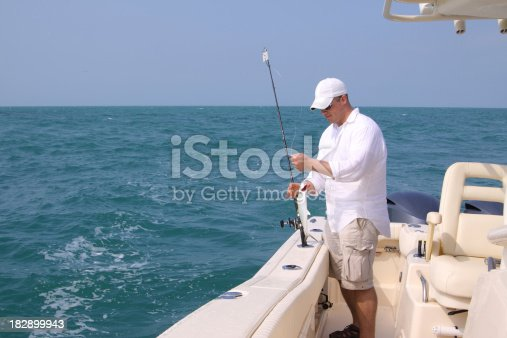 Young man in a boat fishing on the ocean
