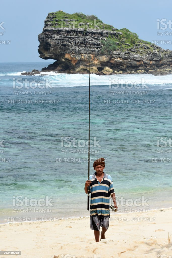 Man fishing on the Watu Karung bech stock photo
