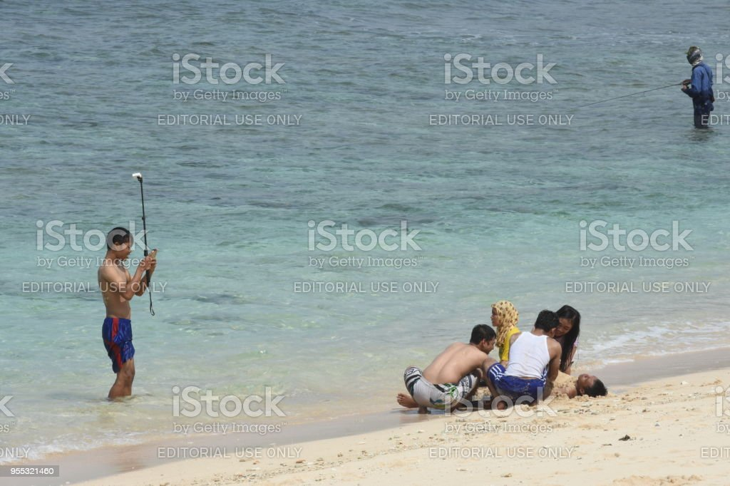 A man fishing on the Watu Karung bech stock photo