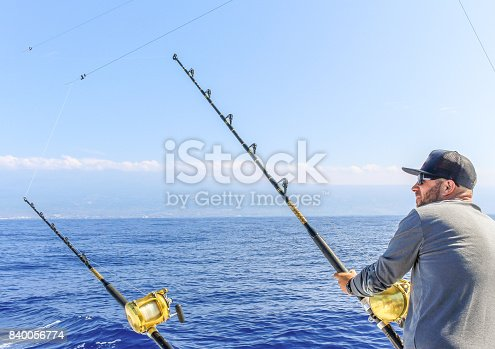 Man and a fishing rod looking out at the ocean, deep sea fishing