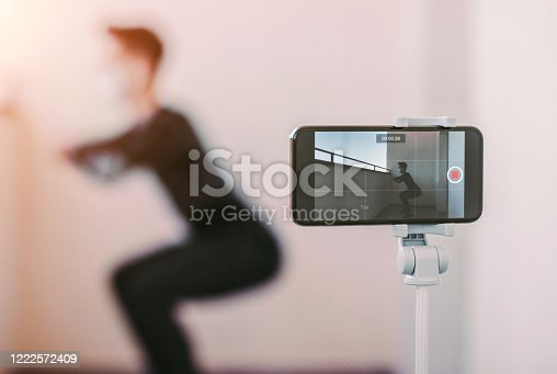 Young sports man in medical face mask record video tutorial for training at home during coronavirus COVID-19 quarantine. Fitness trainer blogger in protective mask squatting in front of phone camera