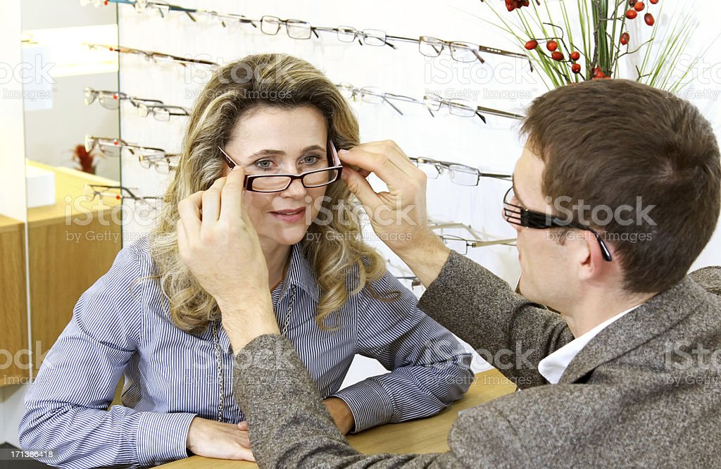 Man fitting a blonde woman with new pair of glasses royalty-free stock photo