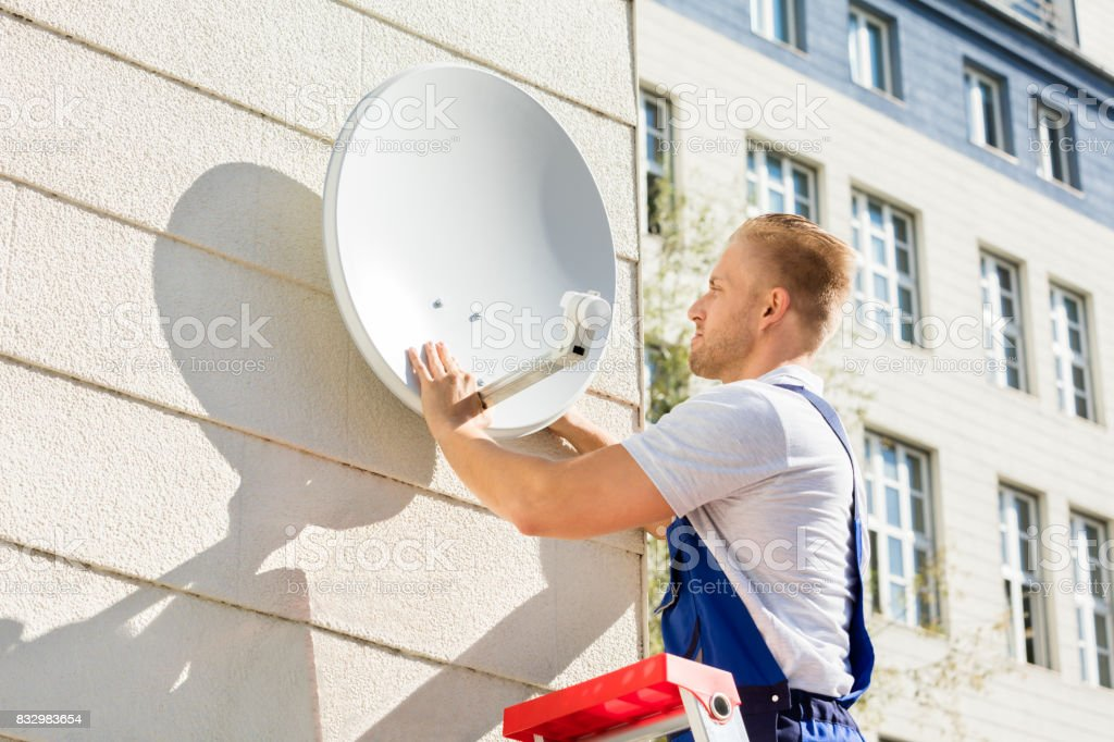 Man Fitting TV Satellite Dish - Stock image .