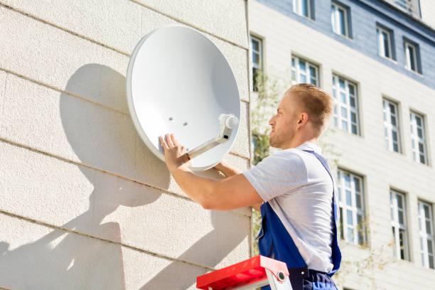 Man Fitting TV Satellite Dish Young Man Fitting TV Satellite Dish To Wall cable tv stock pictures, royalty-free photos & images