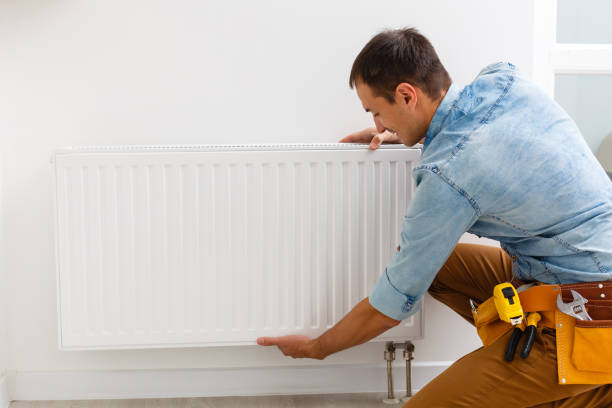 man fixing a heating radiator stock photo
