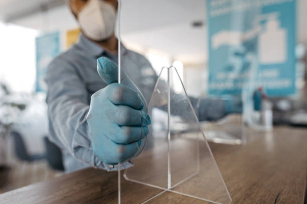 Man fixing acrylic glass at office counter stock photo