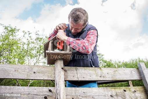 Man Fixing Birdhouse on Wooden Fence