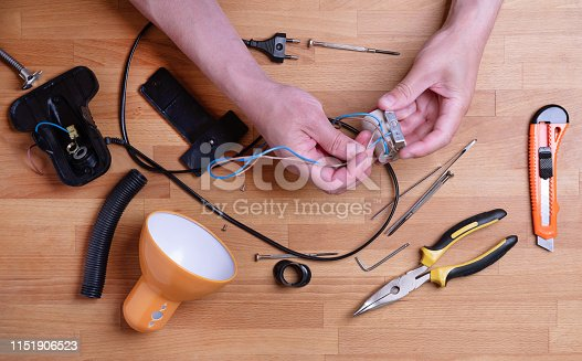 Man fixing desk lamp wires top view. Electrician repairing lights. Technician service workplace concept. Tools and instruments on table. Male hands holding electronic broken parts, details