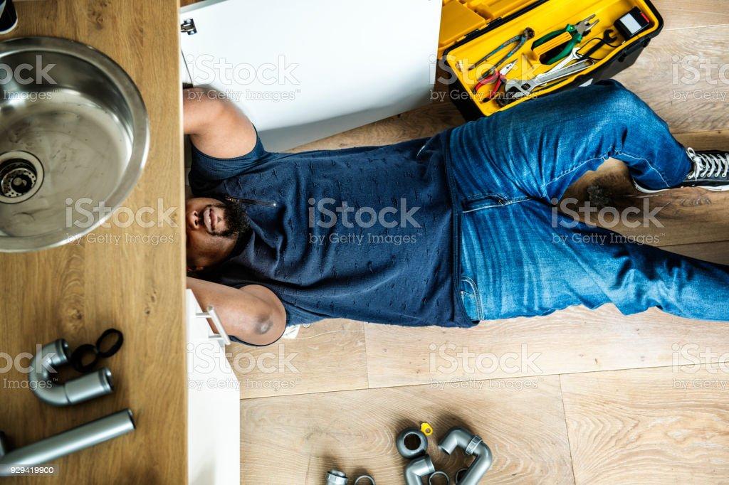 Man fixing kitchen sink stock photo
