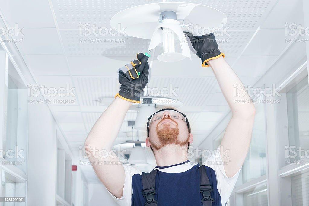 Man Fixing Lamp stock photo