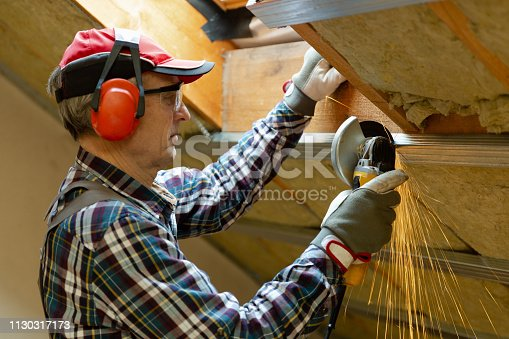 466705128 istock photo Man fixing metal frame using angle grinder on attic ceiling covered with rock wool 1130317173