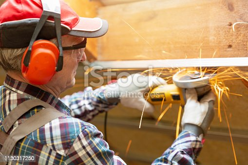 466705128 istock photo Man fixing metal frame using angle grinder on attic ceiling covered with rock wool 1130317250