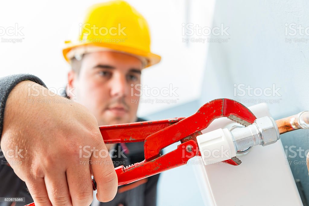 Man fixing radiator stock photo
