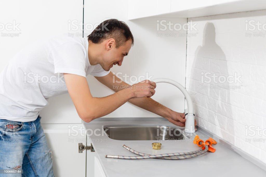 Hombre fijación tubería de fregadero en cocina - foto de stock